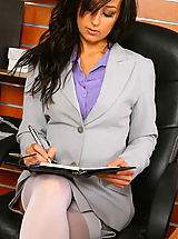 Secretary Pics: Beautiful brunette secretary Laura A strips from her cute grey suit and purple shirt to give us a glimpse of her sexy white lingerie