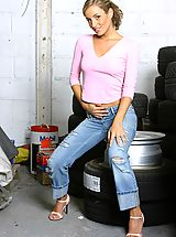 Between Legs, Melanie looking beautiful posing in a car workshop next to a stack of tyres wearing a tight pink top with denim jeans and blue lingerie.