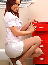 Secretaries, Kinky redhead teases her way out of her work clothes and poses over her desk.